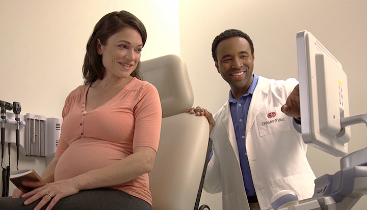Doctor and pregnant woman looking at screen